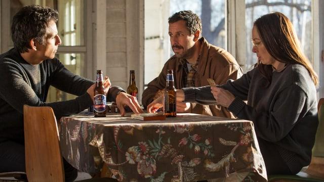 Ben Stiller, Adam Sandler und Elizabeth Marvel sitzen an Tisch.