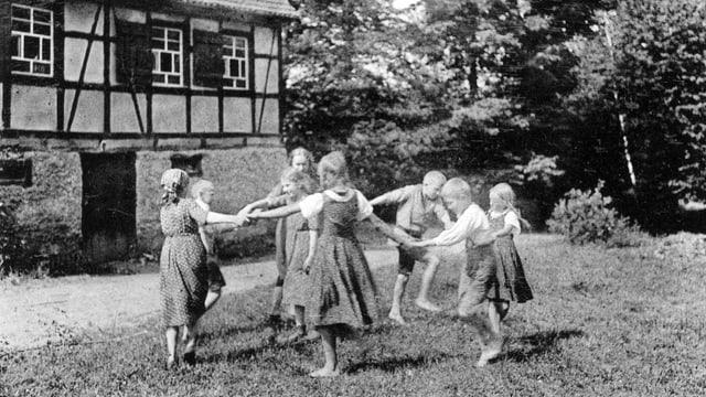 Kinder spielen vor einem Landhaus.