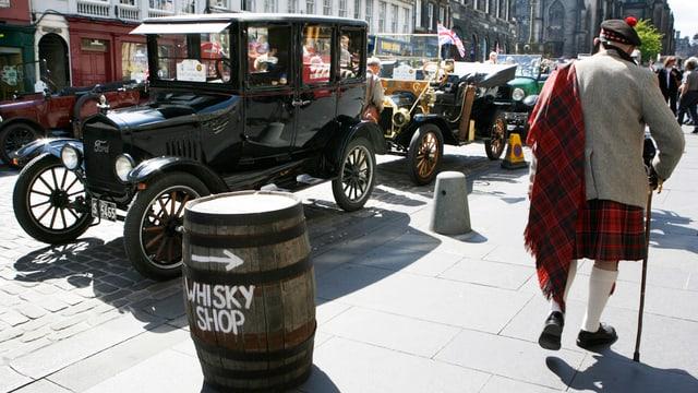 Ein älterer Herr mit Kilt vor einem Fass mit der Aufschrift «Whisky Shop».