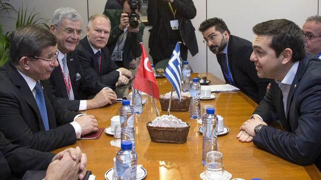 Davutoglu und Tsipras bei einem Vorab-Treffen in Brüssel. Andere Leute am Tisch.