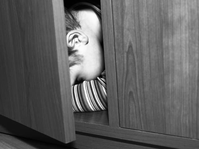 Ein Kind versteckt sich in einem Schrank.