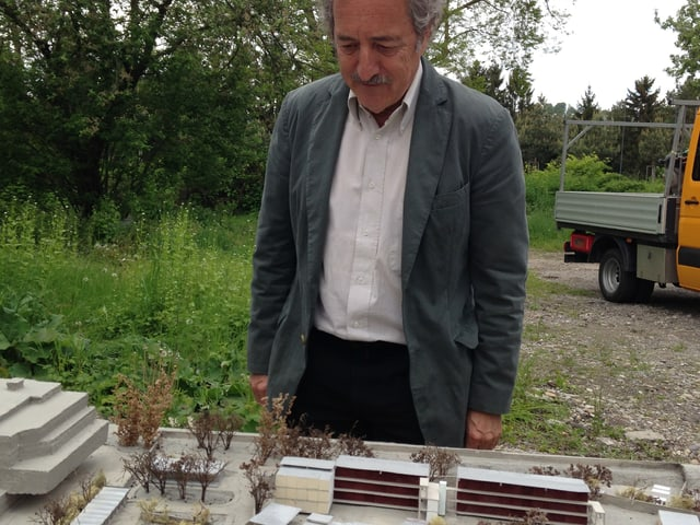 Ein Mann mit Schnauz und grauem Haupthaar in Jackett guckt auf ein Architekturmodell.