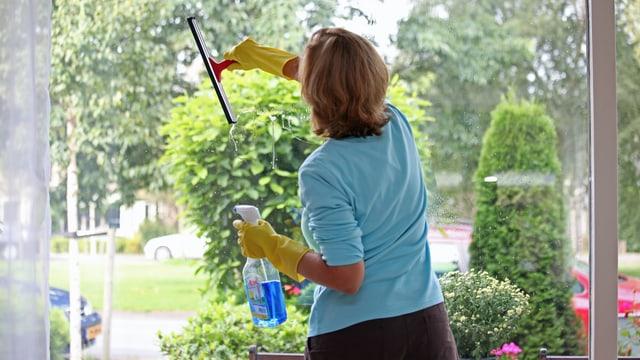 Frau putzt eine Scheibe