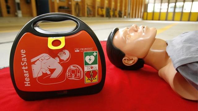 Defibrillator neben Übungspuppe