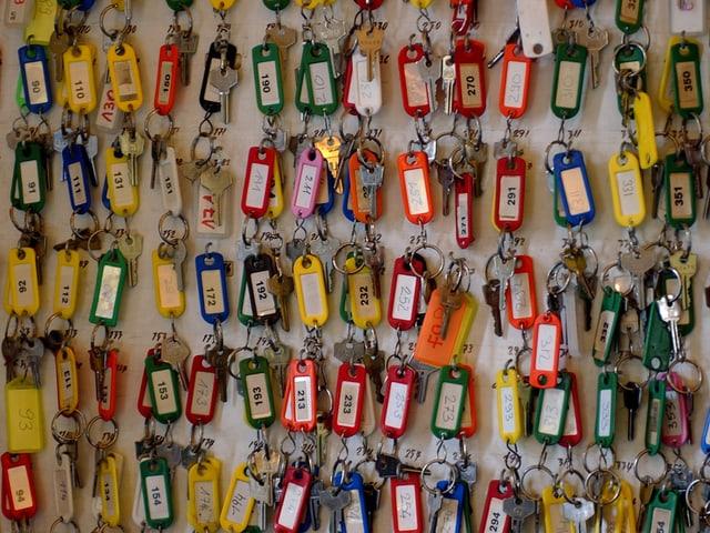 Viele Schlüssel mit bunten Schildern an einem Schlüsselbrett.