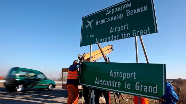 Arbeiter in orangen Westen entfernen das Autobahnschild zum Flughafen in Skopje.