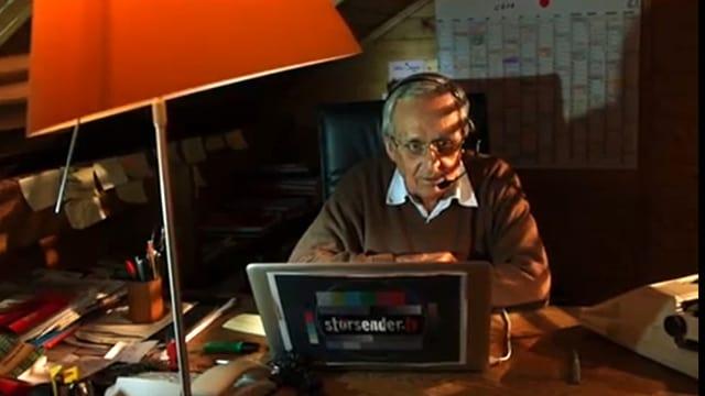 Dieter Hildebrandt sitzt im Lampenschein hinter einem Laptop an einem Schreibtisch. Auf dem Laptop ist der Schriftzug «Störsender» zu lesen.