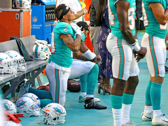 Kenny Stills, Wide Receivers bei den Miami Dolphins, kniet während der Hymne vor der Spielerbank.