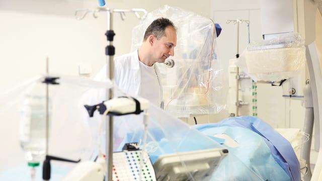 Arzt schaut nach einem Patienten in einem Herzkatheterlabor.