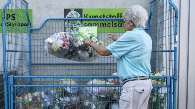 Frau legt Sack mit Plastikabfällen in einen Gitterkasten