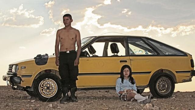Der Mexikaner Heli, die Hauptfigur in Amat Escalantes Film angelehnt an ein Auto in der mexikanischen Wüste, danben sitzt ein Mädchen.