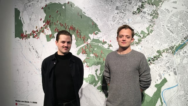 Zwei junge Männer mit kurzen Haaren und schwarzem und grauem Pullover stehen vor einem grossen Stadtplan von Zürich.
