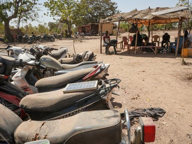Motorräder, im Hintergrund Menschen in Unterstand