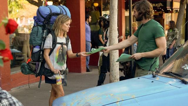 Reese Witherspoon in der Stadt mit riesigem Rucksack erhält Flyer von jungem Mann.