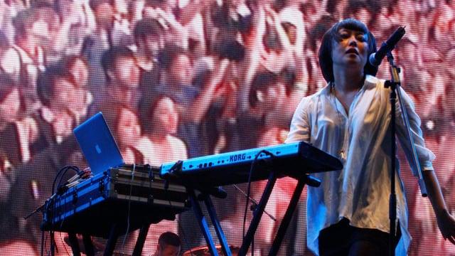 Eine Frau singt auf der Bühne, hinter ihr wird das Publikum auf eine Leinwand projiziert.