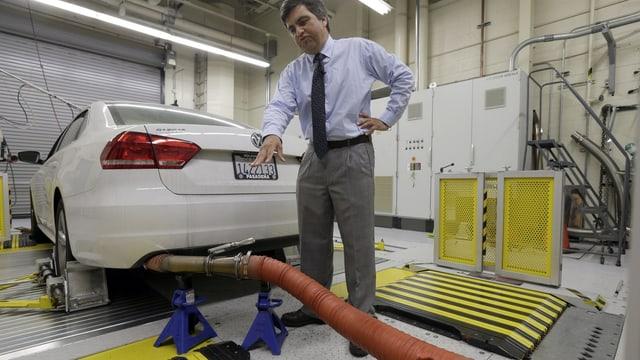 Auto mit Schlauch am Auspuff auf einer Testanlage, hinter dem Auto ein Mann, auf den Auspuff zeigt