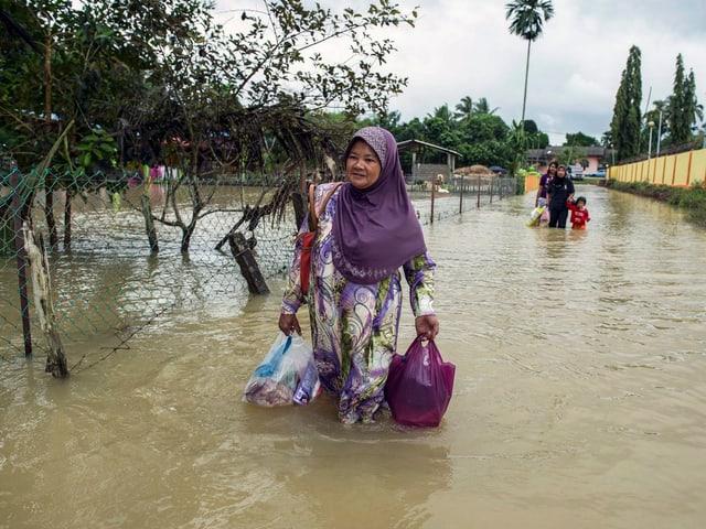 Eine Frau mit zwei Taschen in der Hand geht auf einer überfluteten Strasse.