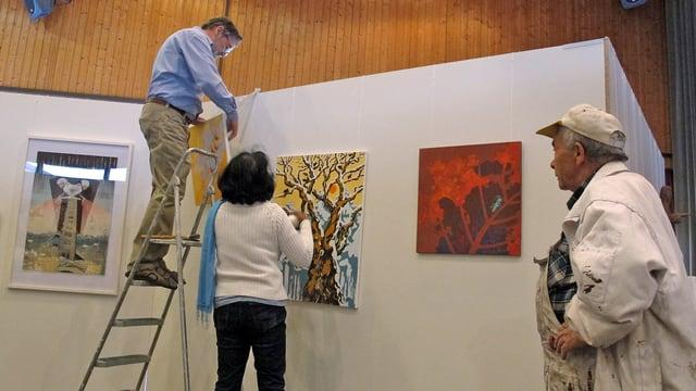 Ein Mann auf einer Leiter und eine Frau am Boden hängen Gemälde auf.