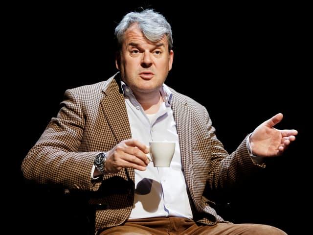 Mike Müller mit Kaffeetasse auf der Bühne.