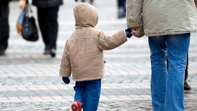 Erwachsene Person hält Kind an der Hand.