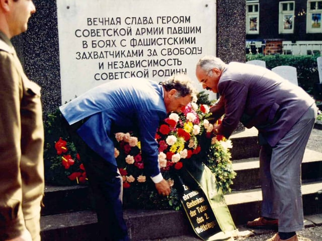 Zwei Männer legen eine Blumenkranz nieder auf einem Grab. Grabstein mit kyrillischer Schrift.