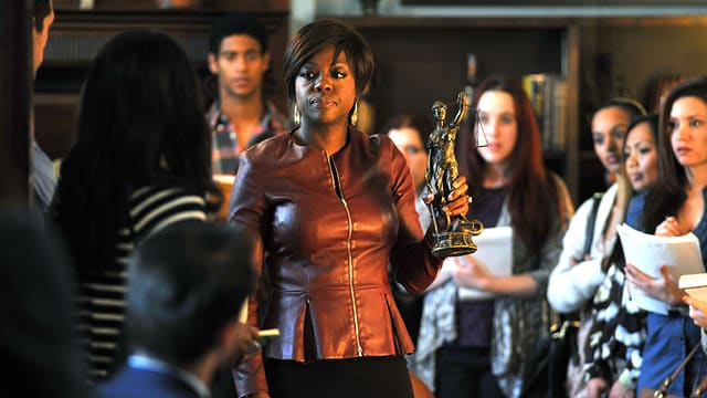 Viola Davis umringt von Studenten. Sie trägt eine braune Lederjeacke und eine goldene Justitia-Figur.