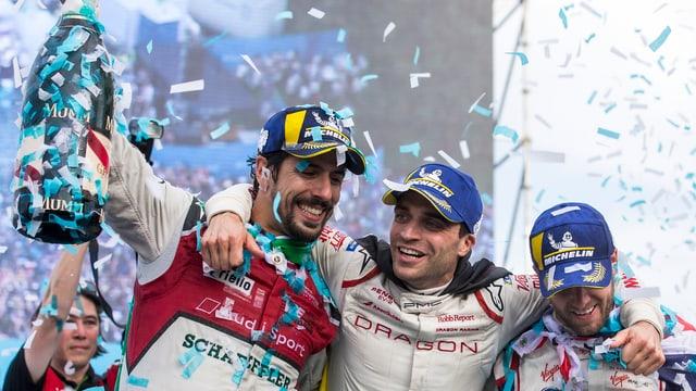 Drei Rennfahrer, eine grosse Champagnerflasche, Konfetti
