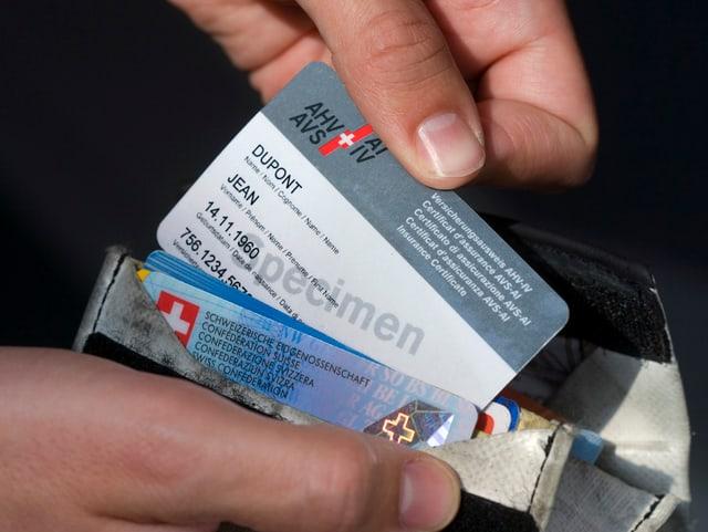Hand zieht AHV-Karte aus Portemonnaie.