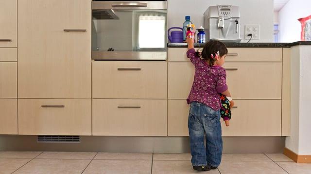 Kind in der Küche holt sich eine Trinkflasche auf der Ablage.