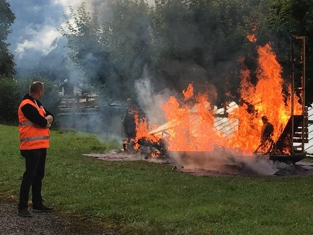 Die Feuerwehr löscht einen Brand auf einem Rasen.