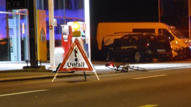 Ein Fahrrad liegt am Boden, im Hintergrund eine Tankstelle, im Vordergrund ein Warn-Dreieck.