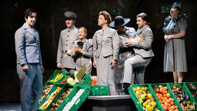 Szene mit sieben Sängerinnen und Sänger in grauen Kostümen.