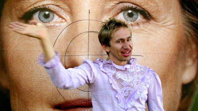 Mann in Bluse und mit Lippenstift vor einem Plakat von Angela Merkel.