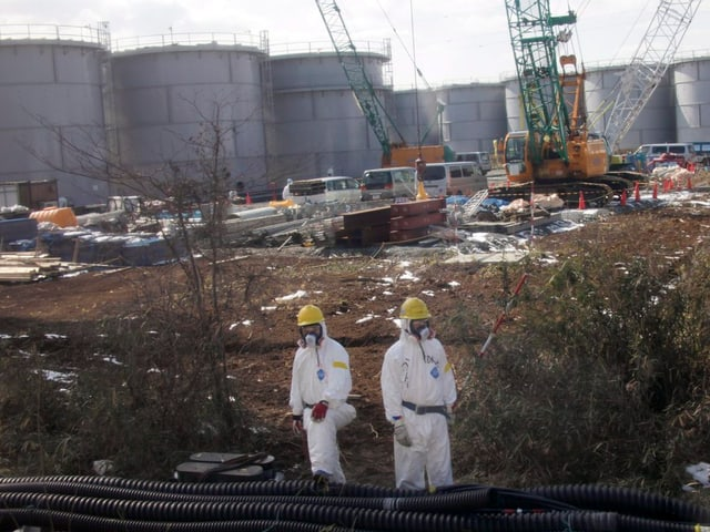 Im Hintergrund mehrere Reaktoren, im Vordergrund zwei Arbeiter in weissen Schutzanzügen mit gelben Helmen