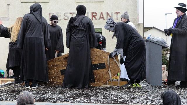 Schwarz gekleidete Figuren versenken einen Sarg in einem Boden aus Konfetti