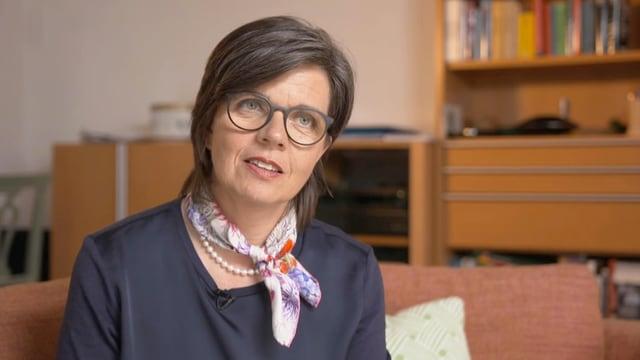 Eine Frau mit Brille und Foulard sitzt auf einem Sofa.