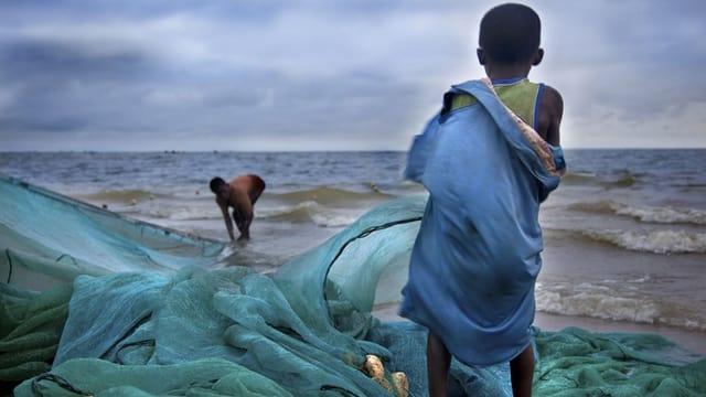 Ein Junge steht mit dem Rücken zum Betrachter auf einem Fischernetz und schaut aufs Meer.