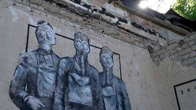 Wandgraffiti mit drei Personen in Gasmasken