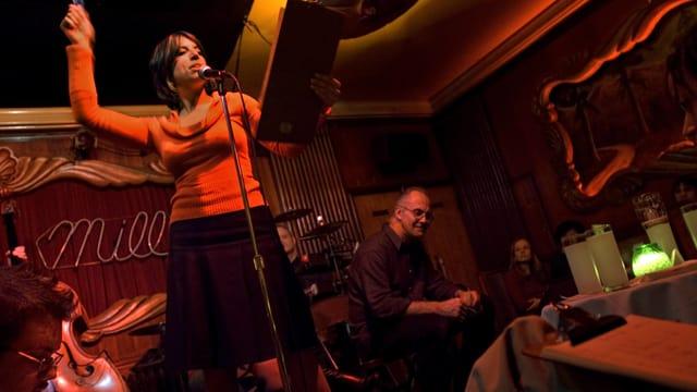 Eine Frau steht referierend auf einer Bühne. Daneben sitzt zuhörend ein Mann.