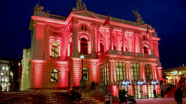 Rot beleuchtetes Opernhaus aus weissem Stein.