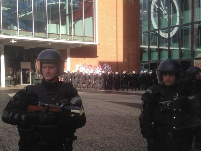 Zwei Polizisten vor der Messe, im Hintergrund weitere Polizisten