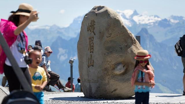 Felsbrocken des chinesischen Berg Emei Shan auf der Rigi. Daneben chinesische Turisten.