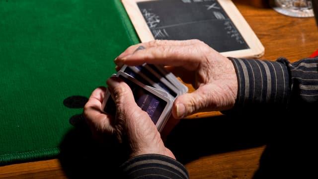 Mann mischelt Jasskarten