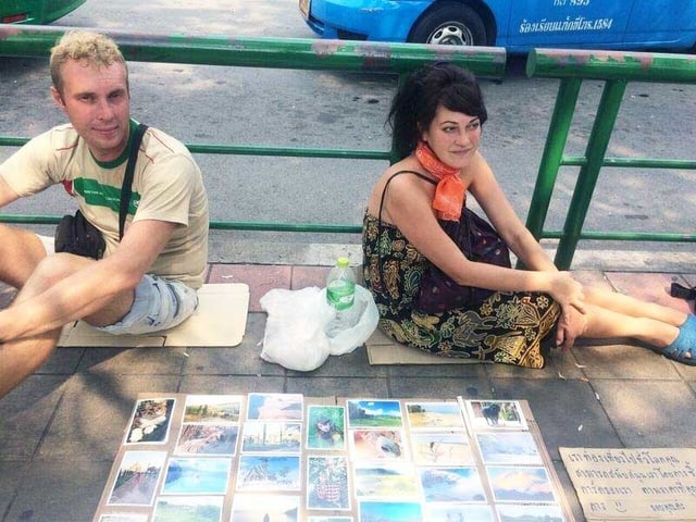 Zwei junge Leute sitzen auf dem Boden auf der Strasse und verkaufen Postkarten.