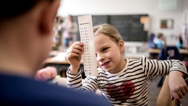 Kinder lernen Kopfrechnen in einem Schulzimmer.