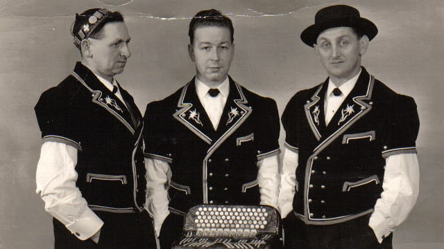 Schwarz-weiss Fotografie mit drei Jodlern in Sennentracht vor einem Akkordeon.