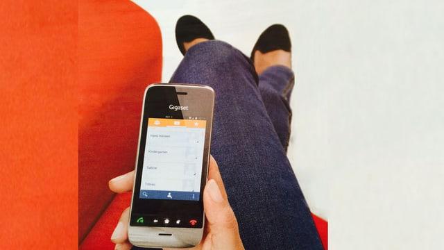 Eine Frau sitzt auf einem Sofa und hält ein schnurloses, smartphone-ähnliches Telefon in der Hand.