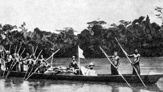 Ein Boot mit zwei Reisenden wird von farbigen Afrikanern mit Stangen durch einen Fluss gelenkt.