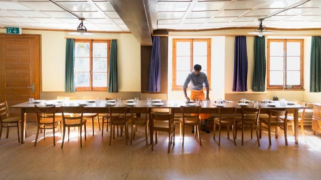 Eine Person deckt einen Tisch in einem Asylzentrum