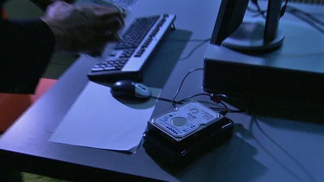 Eine externe Harddisk auf einem Schreibtisch mit Computer (Symbolbild).